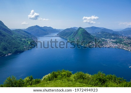 Wide view over the blue water of Lago di Lugano and Monte San Salvatore as seen from Monte Brè, a vantage point near Lugano (Ticino, Switzerland). Foto stock ©