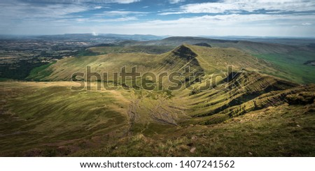 Wide vista of a summer mountain landscape, seen from the top of Pen Y Fan, Brecon Beacons, South Wales, UK, with green grassland, eroded slopes, and blue sky with white clouds. #1407241562