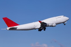 Widebody cargo aircraft departing with blue sky