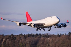 Widebody cargo aircraft landing in front of forest