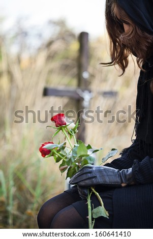 Widow at the cemetary holdig red roses in her hands