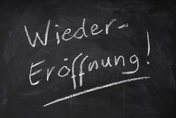 Wiedereröffnung means reopening in German - handwritten text on chalkboard sign
