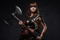 Wielding two handed axe grimy nordic amazon with brown hairs in dark armour posing in dark background.