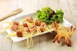 Wiener and Noodle Spider Snacks on Plate with Garnish on Wooden Background