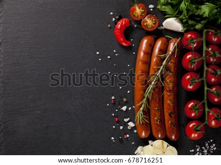 Wiener Sausages with vegetables on black background. Top view.