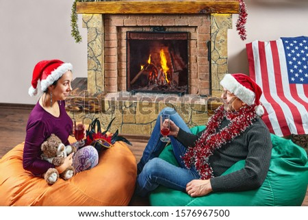 Wife and husband in Santa's hats are drinking wine on bean bag chairs while celebrating New Year. Mature family couple celebrates Christmas near fireplace.