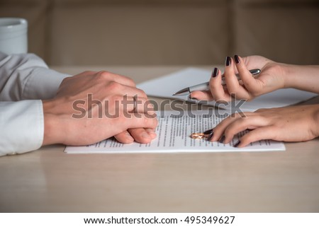 Wife and husband signing divorce (dissolution of marriage) documents, filing divorce papers prepared by lawyer, canceling marriage, performing legal or de jure separation, woman returning wedding ring #495349627