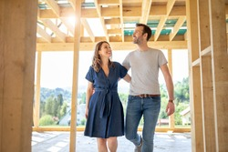 Wife and husband visiting building site of their new house with construction in background