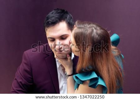 Wife kisses her husband on the cheeks. Young couple in love is kissing in the apartment. #1347022250