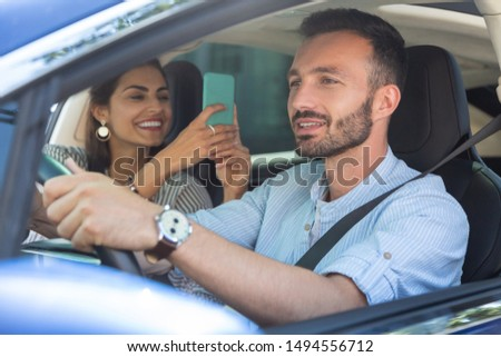 Wife laughing. Wife laughing while making photo of bearded handsome husband driving car #1494556712