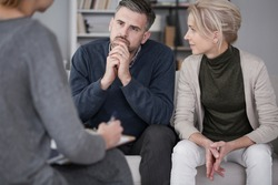 Wife supporting her husband in therapy with the man listening curiously to the counselor in a gray office
