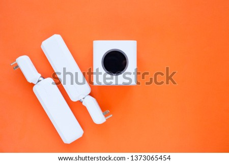 Wifi business concept. Wifi router, access points, mobile phone, laptop, camera and other wireless endpoints on the orange background. Closeup. Space for a text.
