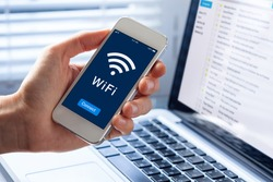 WiFi symbol on smartphone screen with button to connect to wireless internet, close-up of hand holding mobile phone, computer in background