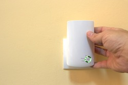 WiFi technology at home, a hand places a white wifi signal repeater into a wall socket
