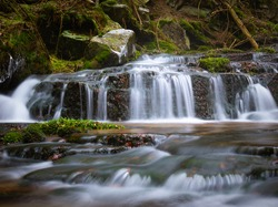 Wild brook with stones and waterfall in Jeseniky mountains, Eastern Europe, Moravia. Clean fresh cold watter, water stream. Long exposure image.