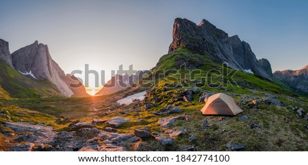 wild camping in the lofoten islands. camping tent among mountains. sunset over camping spot behind polar circle. Panorama of perfect landscape during midnight sun