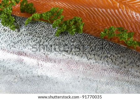 Wild caught trout fillets showing skin and red meat with parsley