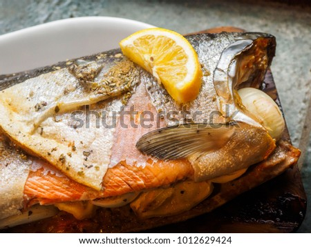 Wild coho salmon grilled by traditional West Coast method on a cedar plank #1012629424