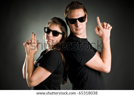 wild couple with sunglasses and finger guns