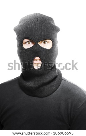 Wild eyed masked bandit concealed under a black textile mask looking in desperation at the camera as he realises that he has been caught in the act