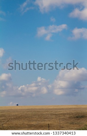 Wild field and blue sky with many different clouds #1337340413