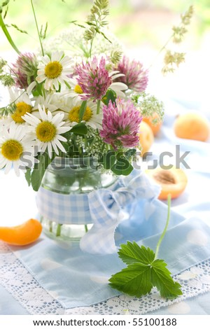 Wild flowers in bank on a table. Bank it is decorated by a self-made bow