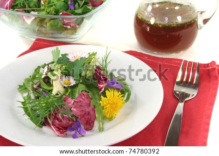 Wild herb salad with balsamic oil dressing on a white background