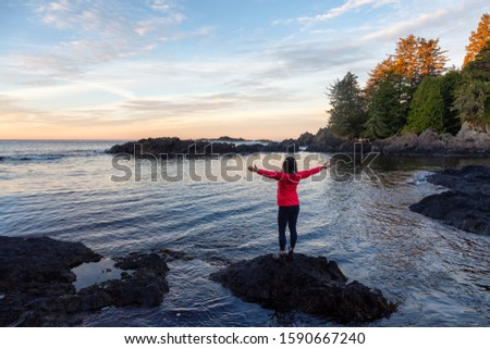 Wild Pacifc Trail, Ucluelet, Vancouver Island, BC, Canada. Adventurous Girl Enjoying the Beautiful View of the Rocky Ocean Coast during a colorful morning sunrise. Concept: Travel, adventure, freedom