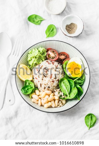 Wild rice, boiled egg, spinach, avocado puree, beans, tomatoes buddha bowl on light background, top view. Healthy vegetarian food concept