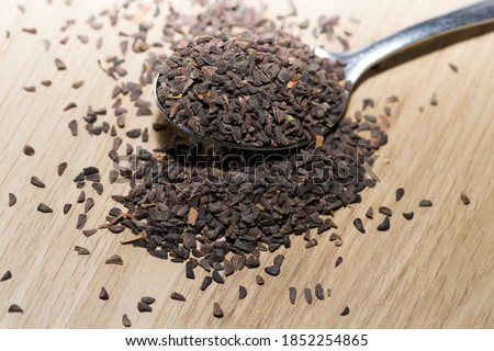 wild rue seeds, Peganum harmala in the spoon on a wooden table Photo stock ©