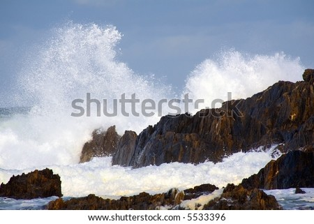 wild surf hitting rocks on the shore