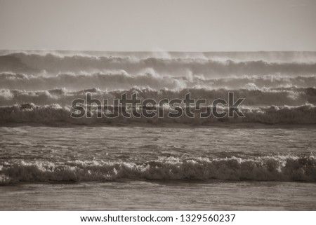 Wild surf with spray and movement, rolls in on the main mount beach at Mount Maunganui, Tauranga, New Zealand, in black and white. #1329560237