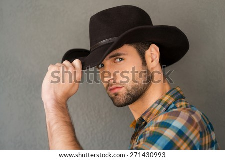 Wild West is his heart. Handsome young man adjusting his cowboy hat and looking at camera while standing against grey background