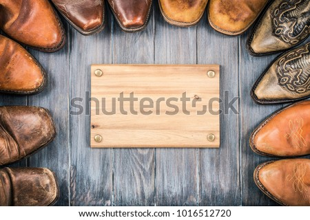 Wild West old retro leather cowboy boots and wooden signboard blank for background. Vintage style filtered photo
