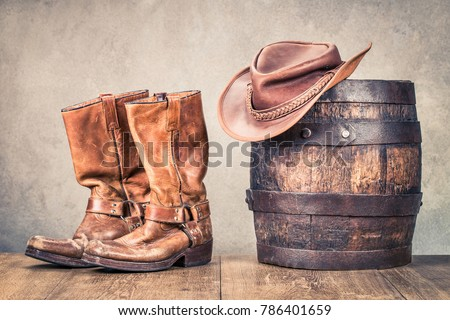 Wild West old retro leather cowboy boots, hat and oak barrel. Vintage style filtered photo