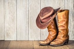 Wild West retro cowboy hat and pair of old leather boots on wooden floor. Vintage style filtered photo