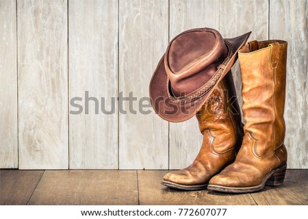 Wild West retro cowboy hat and pair of old leather boots on wooden floor. Vintage style filtered photo - Shutterstock ID 772607077