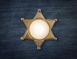 Wild West Sheriff badge on denim background