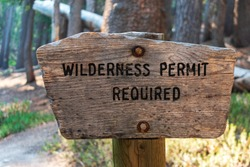 Wilderness permit required signpost on the wooden post in the national forest.