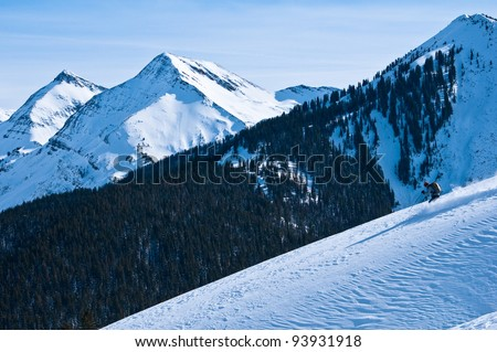 Wilderness Snow Skier: a mature woman skiing un-tracked powder slope in colorado with majestic mountain background near Aspen, CO.
