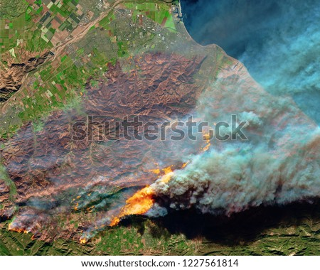 Wildfire Camp burns out from aerial above in California. Fire and smoke. Forest fire. Black smoke and orange fire view from space. California Camp wildfire. Satellite view California USA.