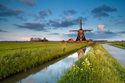 wildflowers and dutch windmill by river at sunrise, Groningen, Netherlands
