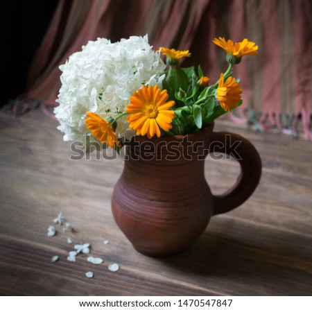 Wildflowers in a clay jug. Still life with flowers.