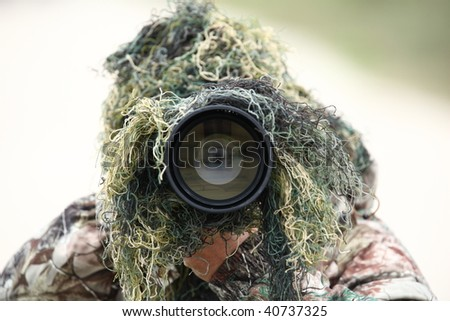 https://image.shutterstock.com/display_pic_with_logo/288118/288118,1257936043,2/stock-photo-wildlife-photographer-using-camouflage-and-pointing-his-huge-mm-lens-at-you-while-outdoors-40737325.jpg