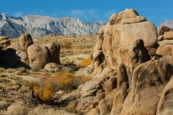 Wildly eroded rock formations of the Alabama hills and Mount Whitney at the back on a sunny spring day in Lone Pine, California