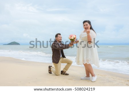 Will you marry me concept, Asian man on his knees asking his girlfriend to marry on the beach.
