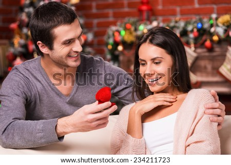 Will you marry me? Handsome young man making a proposal while giving an engagement ring to his girlfriend with Christmas Decoration in the background