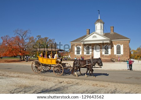 WILLIAMSBURG, VIRGINIA - NOVEMBER 9: A horse-drawn carriage rides by the courthouse in Colonial Williamsburg, a major attraction for tourists and meetings of world leaders, on November 9, 2011.