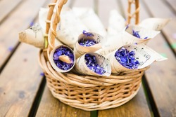 Willow basket filled with paper cornets with dry violet lavender flowers, wooden background
