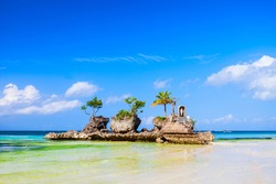 Willy's Rock is a tidal island with a statue of the Virgin Mary at the Boracay beach in Philippines